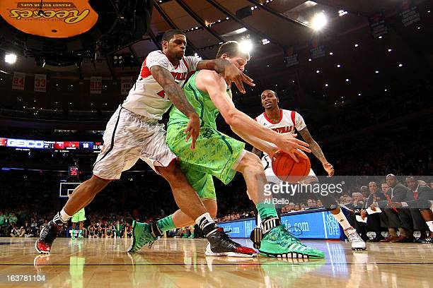 Jack Cooley of the Notre Dame Fighting Irish fights for control of the ball against Chane Behanan of the Louisville Cardinals during the semifinals...