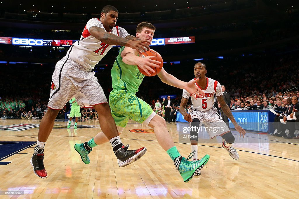 Jack Cooley (C) #45 of the Notre Dame Fighting Irish fights for control of the ball against Chane Behanan #21 of the Louisville Cardinals during the semifinals of the Big East Men's Basketball Tournament at Madison Square Garden on March 15, 2013 in New York City.