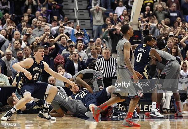 Jack Cooley of the Notre Dame Fighting Irish celebrates the win as Ryan Boatright of the Connecticut Huskies walks off the court on January 29 2012...