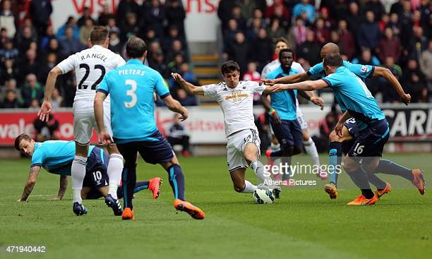 Jack Cork of Swansea attempts to get past Charlie Adam and Jonathan Walters of Stoke City during the Premier League match between Swansea City and...