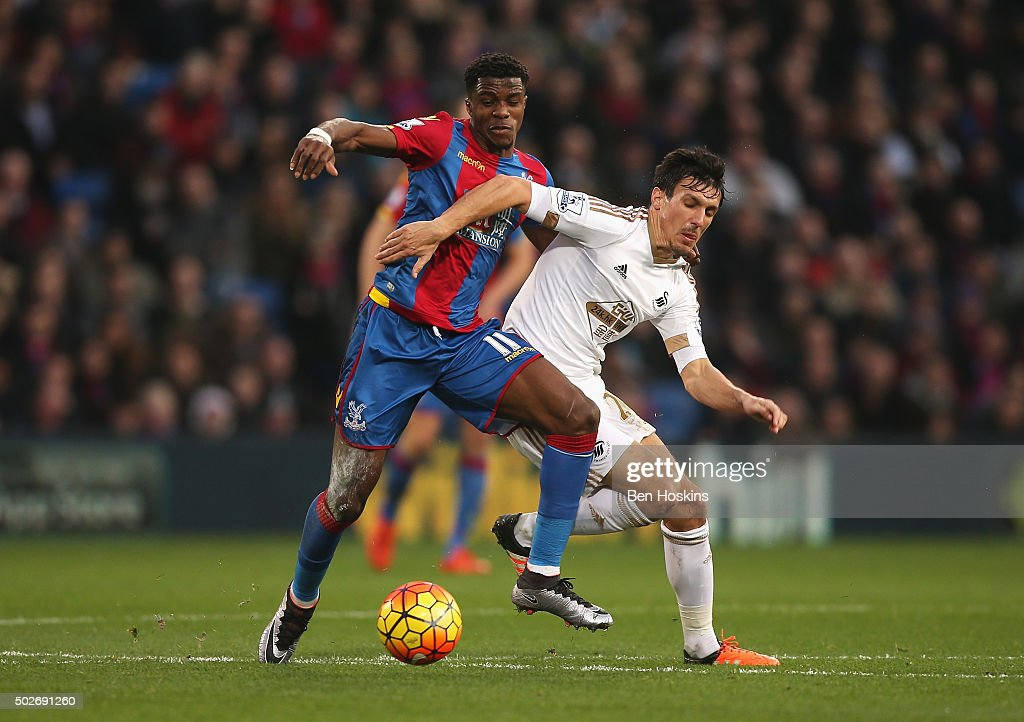 Jack Cork of Swansea City and Wilfried Zaha of Crystal Palace compete for the ball during the Barclays Premier League match between Crystal Palace and Swansea City at Selhurst Park on December 28, 2015 in London, England.
