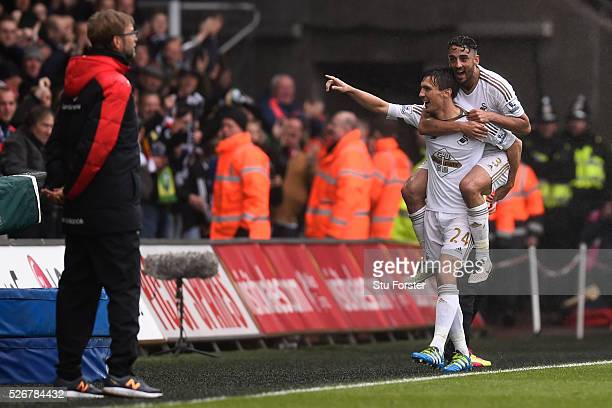 Jack Cork of Swansea City celebrates scoring his team's second goal with Neil Taylor as Jurgen Klopp manager of Liverpool looks on during the...