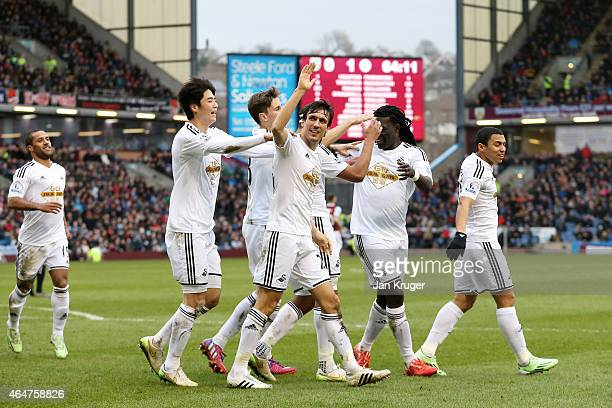 Jack Cork of Swansea City is congratulated by teamates after his shot is deflected for an own goal during the Barclays Premier League match between...