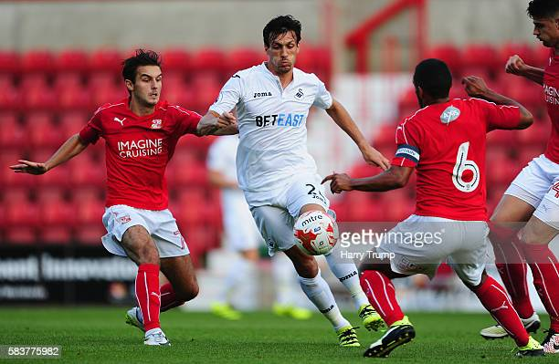 Jack Cork of Swansea City is tackled by John Goddard of Swindon Town during the Pre Season Friendly match between Swindon Town and Swansea City at...