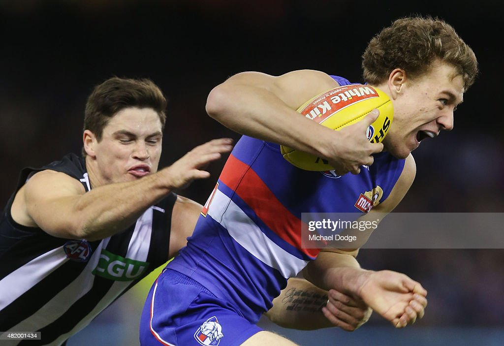 Jack Crisp of the Magpies misses a tackle on Jackson Macrae of the Bulldogs during the round 17 AFL match between the Western Bulldogs and the Collingwood Magpies at Etihad Stadium on July 26, 2015 in Melbourne, Australia.