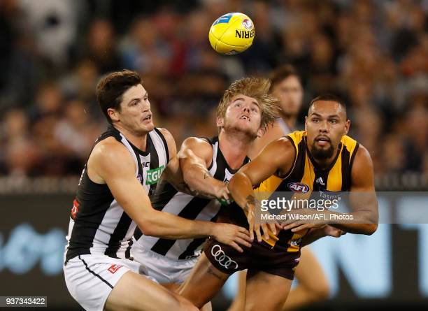 Jack Crisp of the Magpies Sam Murray of the Magpies and Jarman Impey of the Hawks compete for the ball during the 2018 AFL round 01 match between the...