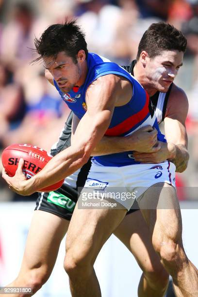 Jack Crisp of the Magpies tackles Easton Wood of the Bulldogs during the JLT Community Series AFL match between Collingwood Magpies and the Western...