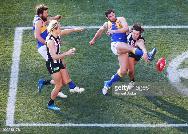 Jack Darling of the Eagles kicks the ball past Matthew Scharenberg of the Magpies during the round 17 AFL match between the Collingwood Magpies and...