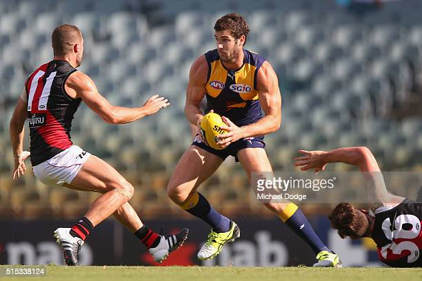 Jack Darling of the Eagles runs with the ball past David Zaharakis of the Bombers and Michael Hartley during the NAB Challenge AFL match between the...