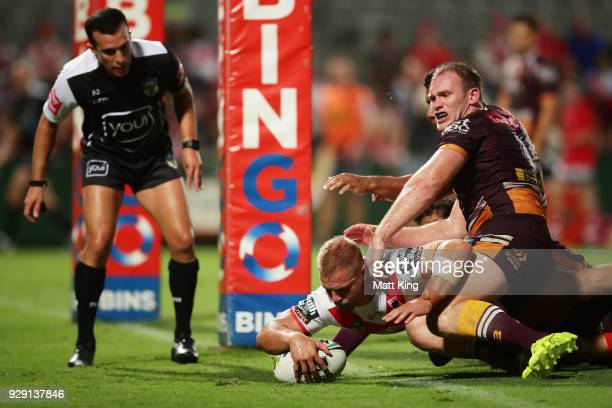 Jack De Belin of the Dragons beats Matthew Lodge of the Broncos to score a try during the round one NRL match between the St George Illawarra Dragons...