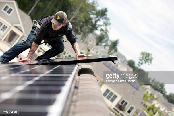 Jack Doherty photovoltaic project manager for Revision Energy installs a solar panel on a home at OceanView at Falmouth The company which employs...