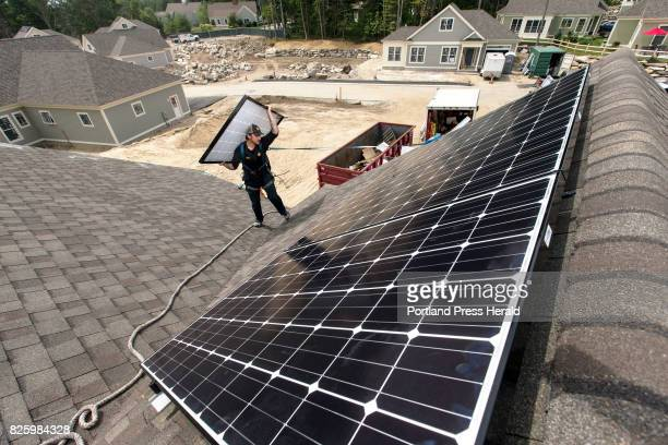 Jack Doherty photovoltaic project manager for Revision Energy carries a solar panel to the roof ridge of a home at OceanView at Falmouth The company...
