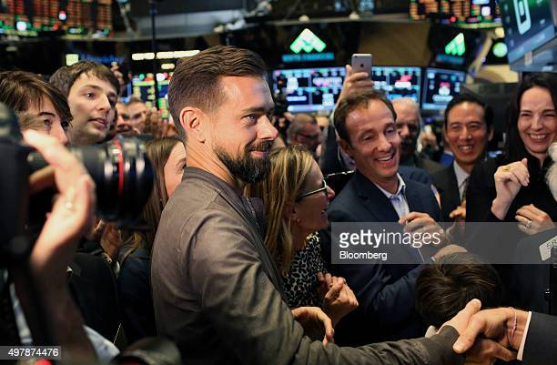 Jack Dorsey chief executive officer of Square Inc center shakes hands with a man while touring the floor of the New York Stock Exchange in New York...