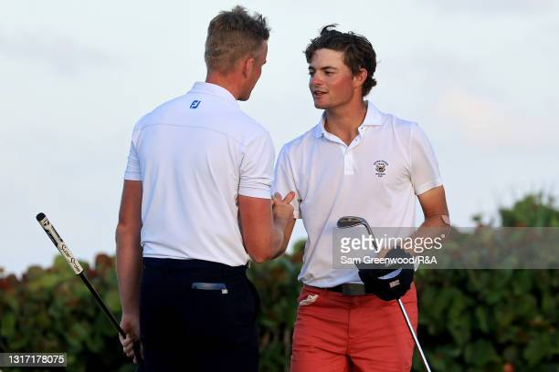 Jack Dyer of Team Great Britain and Ireland and Tyler Strafaci of Team USA shake hands on the 18th green after Dyer won their match during Sunday...