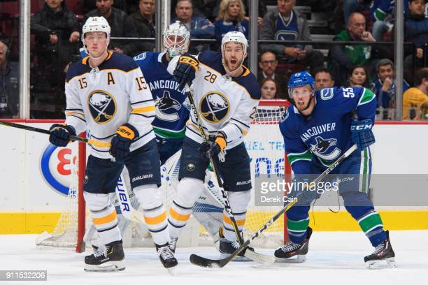 Jack Eichel and Zemgus Girgensons of the Buffalo Sabres stand in front of Jacob Markstrom as Alex Biega of the Vancouver Canucks defends during their...
