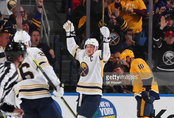 Jack Eichel of the Buffalo Sabres celebrates his second period goal as Colton Sissons of the Nashville Predators reacts during an NHL game on...