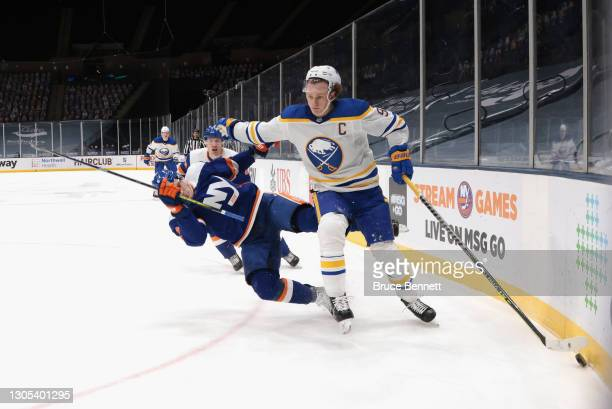 Jack Eichel of the Buffalo Sabres fights off Ryan Pulock of the New York Islanders during the first period at the Nassau Coliseum on March 04, 2021...