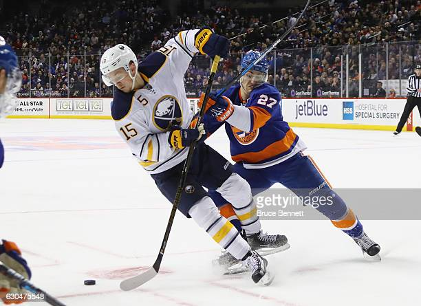 Jack Eichel of the Buffalo Sabres is checked by Anders Lee of the New York Islanders during the first period at the Barclays Center on December 23...