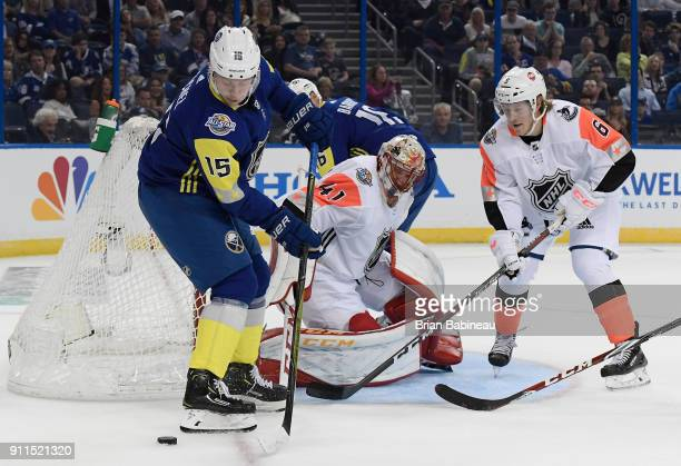 Jack Eichel of the Buffalo Sabres plays the puck at the side of the net as goaltender Mike Smith of the Calgary Flames and Brock Boeser of the...