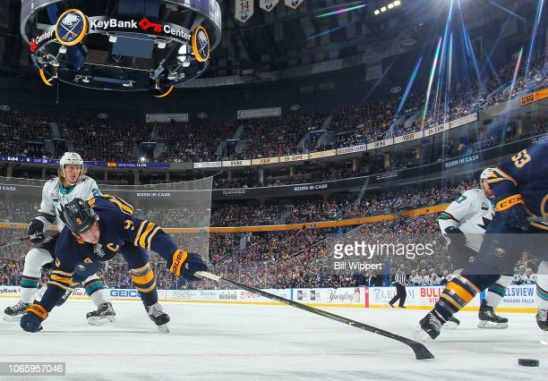 Jack Eichel of the Buffalo Sabres reaches for the puck tailed by Marcus Sorensen of the San Jose Sharks during an NHL game on November 27 2018 at...