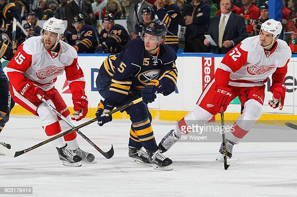 Jack Eichel of the Buffalo Sabres skates between Riley Sheahan and Jonathan Ericsson of the Detroit Red Wings during an NHL game on January 2 2016 at...