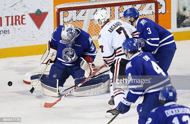 Jack Flinn of the Mississauga Steelheads makes a save on Mikkel Aagaard of the Niagara IceDogs during an OHL game at the Meridian Centre on October...