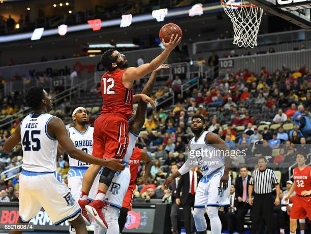 Jack Gibbs of the Davidson Wildcats drives to the hoop in front of Nicola Akele of the Rhode Island Rams during the semifinals of the Atlantic 10...