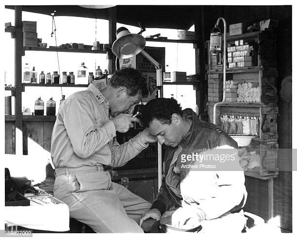 Jack Gilford examines Alan Arkin's ears in a scene from the film 'Catch22' 1970
