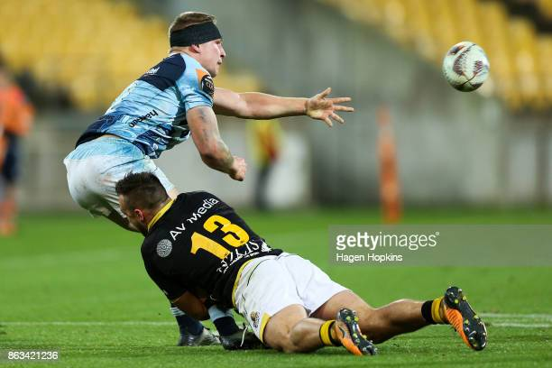 Jack Goodhue of Northland offloads in the tackle of Wes Goosen of Wellington during the Mitre 10 Cup Semi Final match between Wellington and...