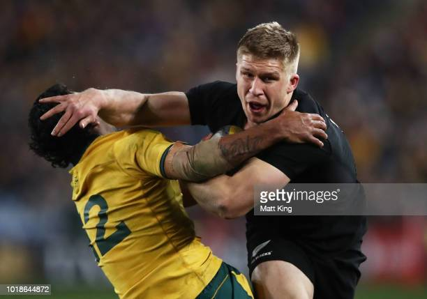Jack Goodhue of the All Blacks puts a fend on Kurtley Beale of the Wallabies during The Rugby Championship Bledisloe Cup match between the Australian...