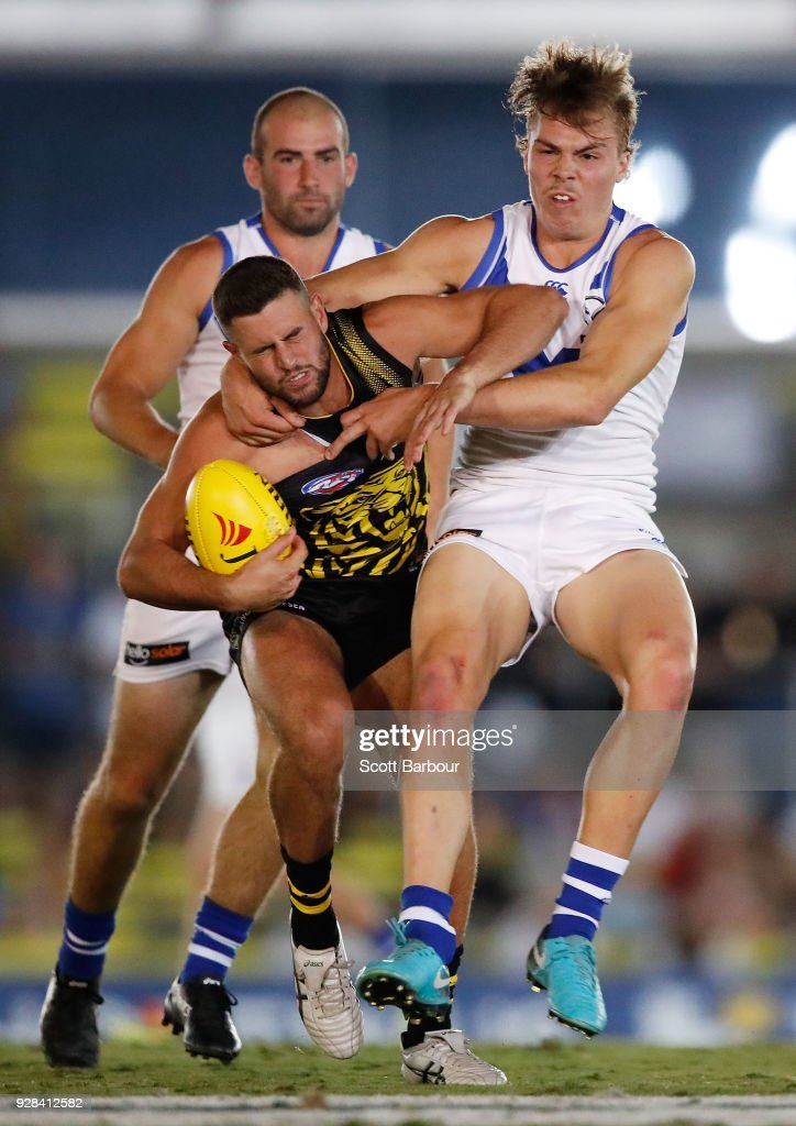 Jack Graham of the Tigers is tackled by Cameron Zurhaar of the Kangaroos during the AFL JLT Community Series match between the Richmond Tigers and the North Melbourne Kangaroos at Ikon Park on March 7, 2018 in Melbourne, Australia.