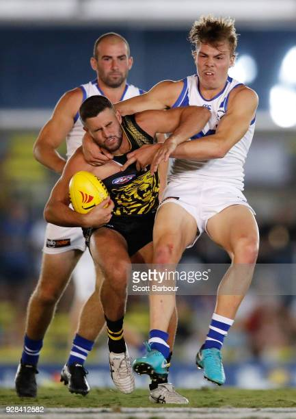 Jack Graham of the Tigers is tackled by Cameron Zurhaar of the Kangaroos during the AFL JLT Community Series match between the Richmond Tigers and...