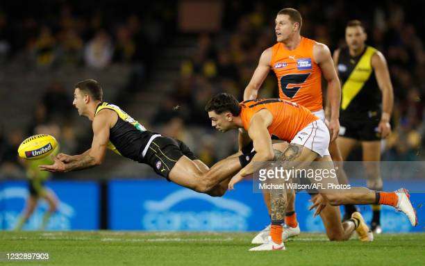Jack Graham of the Tigers is tackled by Tim Taranto of the Giants during the 2021 AFL Round 09 match between the Richmond Tigers and the GWS Giants...