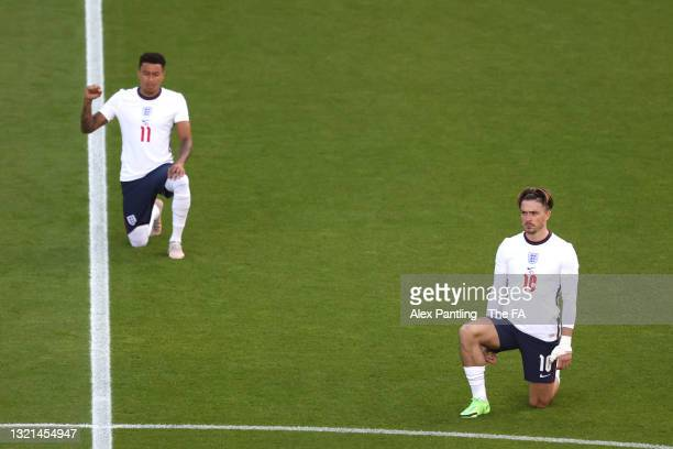 Jack Grealish and Jesse Lingard of England take a knee in support of the black lives matter movement during the international friendly match between...