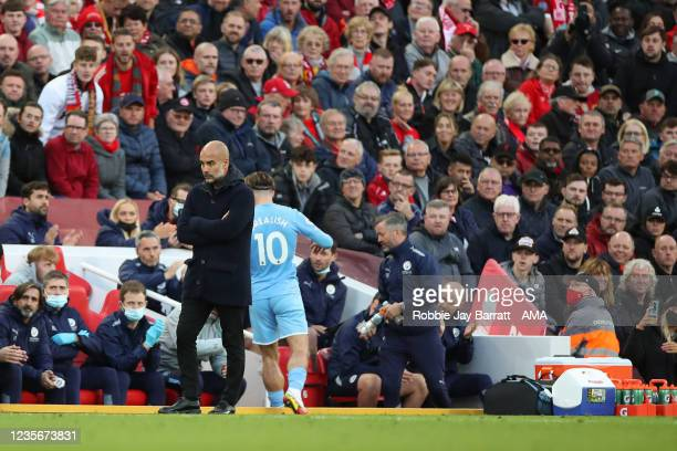 Jack Grealish is taken off by Pep Guardiola the head coach / manager of Manchester City during the Premier League match between Liverpool and...