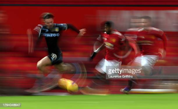 Jack Grealish of Aston Villa battles for possession with Fred and Luke Shaw of Manchester United during the Premier League match between Manchester...