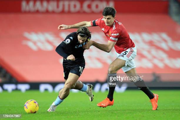 Jack Grealish of Aston Villa battles for possession with Harry Maguire of Manchester United during the Premier League match between Manchester United...