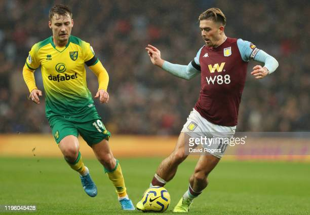 Jack Grealish of Aston Villa battles for the ball with Tom Trybull of Norwich City during the Premier League match between Aston Villa and Norwich...