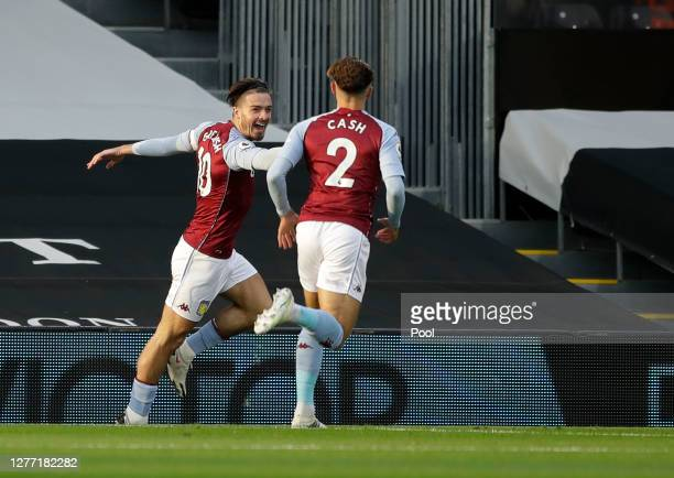 Jack Grealish of Aston Villa celebrates with teammate Matty Cash after scoring his team's first goal during the Premier League match between Fulham...