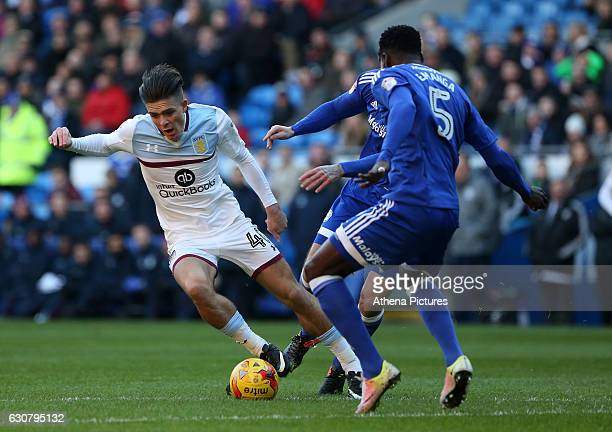 Jack Grealish of Aston Villa is challenged by Captian Sean Morrison and Bruno Ecuele Manga of Cardiff City during the Sky Bet Championship match...