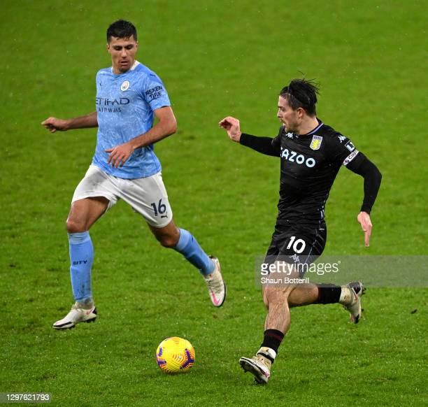 Jack Grealish of Aston Villa is challenged by Rodri of Manchester City during the Premier League match between Manchester City and Aston Villa at...