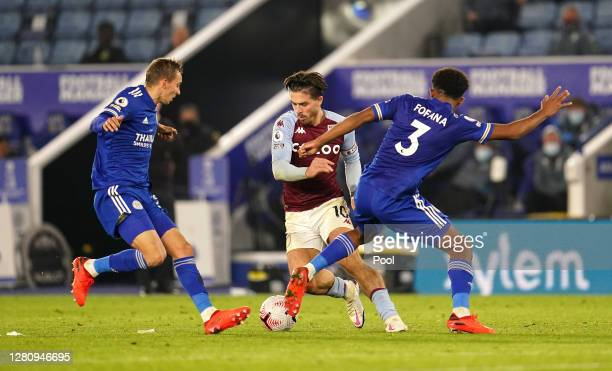 Jack Grealish of Aston Villa is challenged by Timothy Castagne and Wesley Fofana of Leicester City during the Premier League match between Leicester...