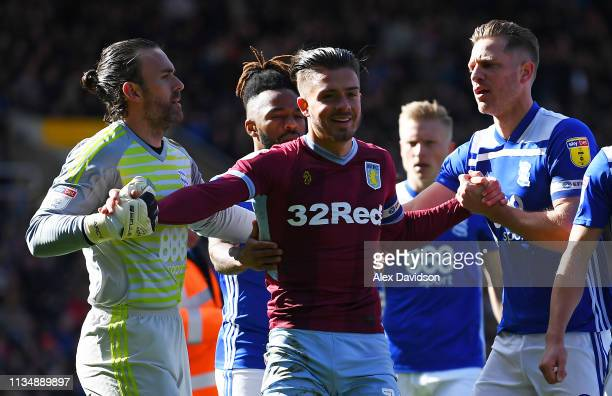 Jack Grealish of Aston Villa is helped up by Lee Camp and Michael Morrison of Birmingham City after colliding with a pitch invader during the Sky Bet...
