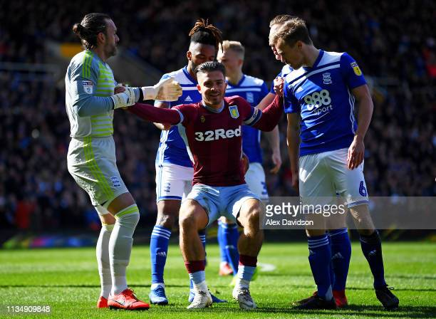 Jack Grealish of Aston Villa is helped up by Lee Camp of Birmingham City and Maikel Kieftenbeld of Birmingham City after being struck by a fan during...