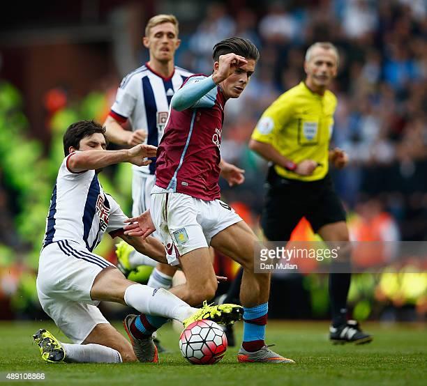 Jack Grealish of Aston Villa is tackled by Claudio Yacob of West Bromwich Albion during the Barclays Premier League match between Aston Villa and...
