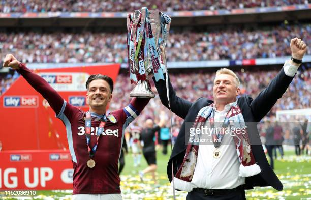 Jack Grealish of Aston Villa lifts the trophy with Dean Smith of Aston Villa following victory in the Sky Bet Championship Playoff Final match...