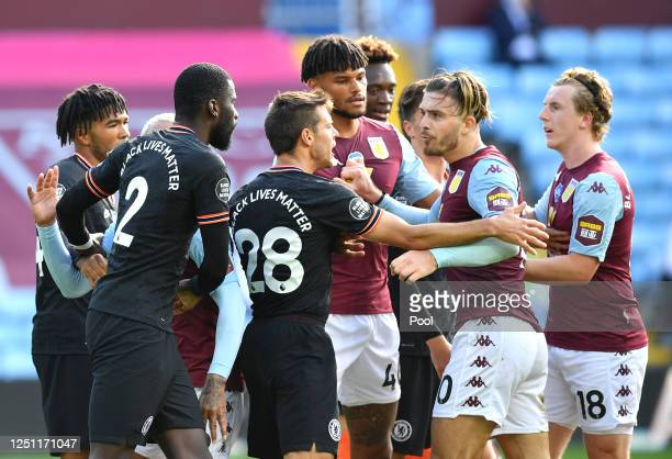 Jack Grealish of Aston Villa reacts towards Antonio Rudiger of Chelsea as players hold each other back during the Premier League match between Aston...