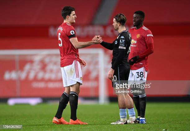 Jack Grealish of Aston Villa shakes hands with Harry Maguire of Manchester United following the Premier League match between Manchester United and...
