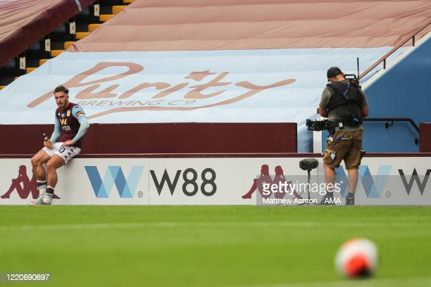 Jack Grealish of Aston Villa sits on the sponsor boards to have a drink during the Premier League match between Aston Villa and Sheffield United at...