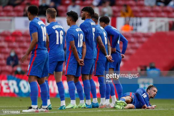 Jack Grealish of England lies behind the wall as they prepare to defend a free kick during the international friendly match between England and...